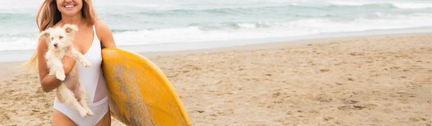 Mujer sosteniendo una tabla de surf y un perro en la playa.