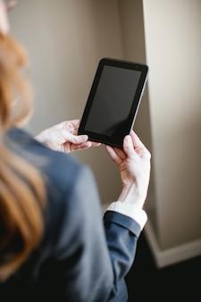 Mujer sosteniendo tablet o smartphone con manos, pantalla negra
