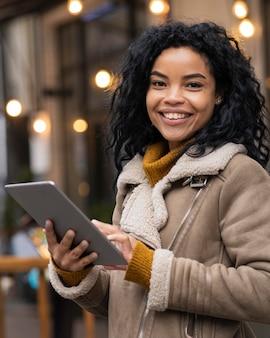 Mujer sosteniendo una tableta fuera