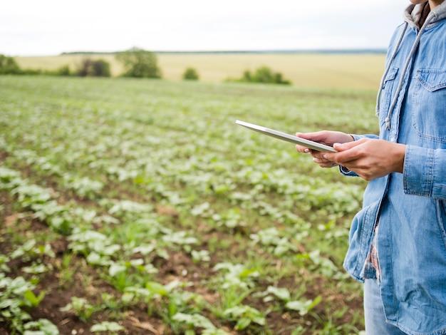Mujer sosteniendo una tableta junto a un campo agrícola con espacio de copia