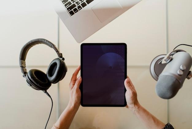 Mujer sosteniendo una tableta por un micrófono de estudio para grabar