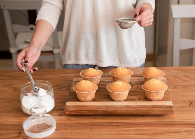 Mujer sosteniendo tamiz preparándose para espolvorear muffins con azúcar