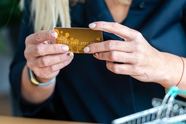 Mujer sosteniendo una tarjeta de crédito en la mano, mini carrito de compras en el fondo, concepto de pago sin efectivo