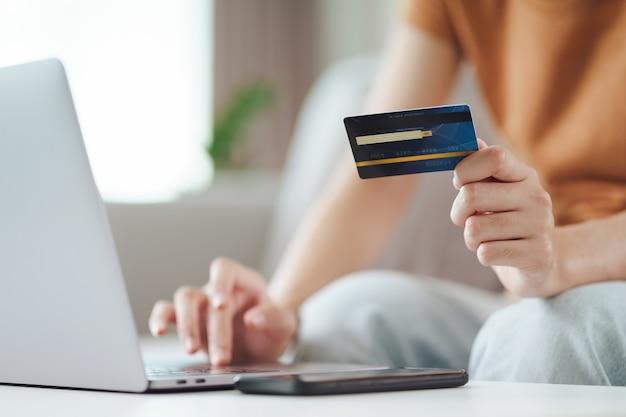 Mujer sosteniendo una tarjeta de crédito y usando una computadora portátil compras en línea banca por internet