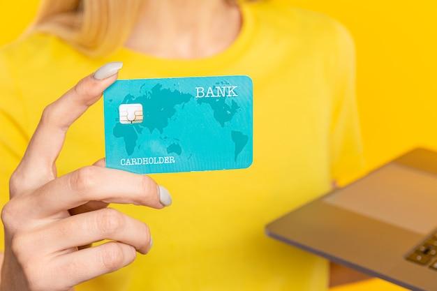 La mujer está sosteniendo una tarjeta de crédito y está usando una computadora portátil