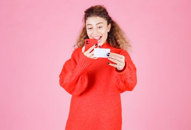 Mujer sosteniendo una tarjeta de visita y llamando al número que figura en ella.