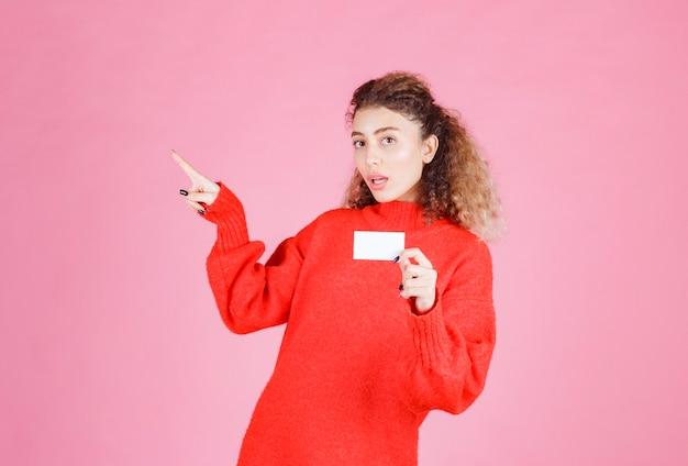 Mujer sosteniendo una tarjeta de visita y presentando a su colega.