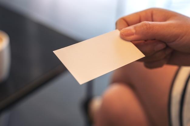 Una mujer sosteniendo una tarjeta de visita vacía.