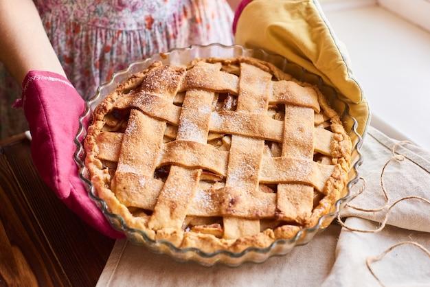 Una mujer sosteniendo una tarta de manzana recién horneada. mujer poniendo delicioso pastel americano en la mesa. la ama de casa en los guantes de cocina entrega la tarta de manzana a la mesa.