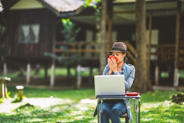 Mujer sosteniendo una taza de café y bebiendo en la mañana y trabajando en la computadora portátil