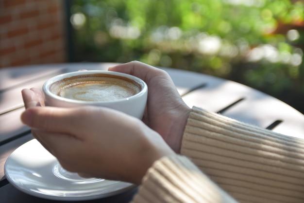Mujer sosteniendo una taza de café en el café
