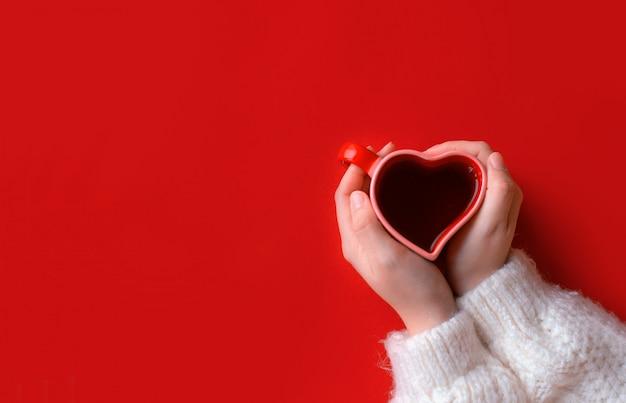 Mujer sosteniendo una taza de café caliente, con corazón