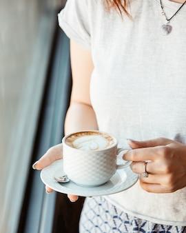 Mujer sosteniendo una taza de café frente a la ventana