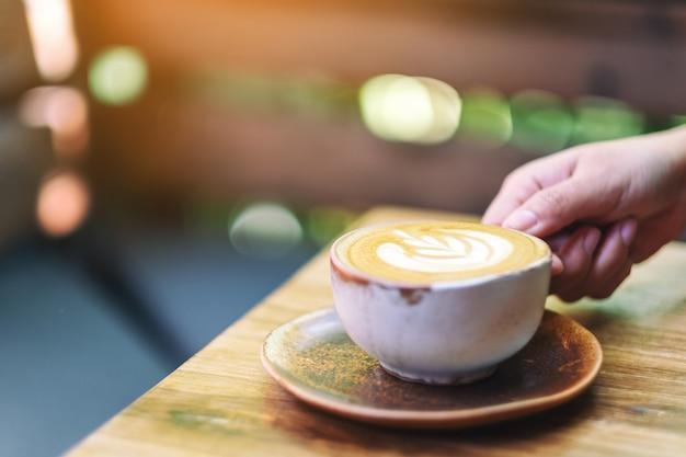 Una mujer sosteniendo una taza de café con leche caliente en la mesa de madera en la mañana