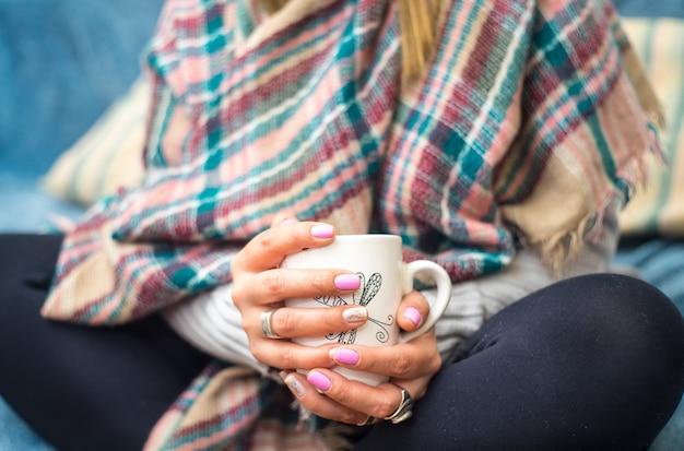 Mujer sosteniendo una taza de café vestida con ropa de invierno abrigada mientras está sentado