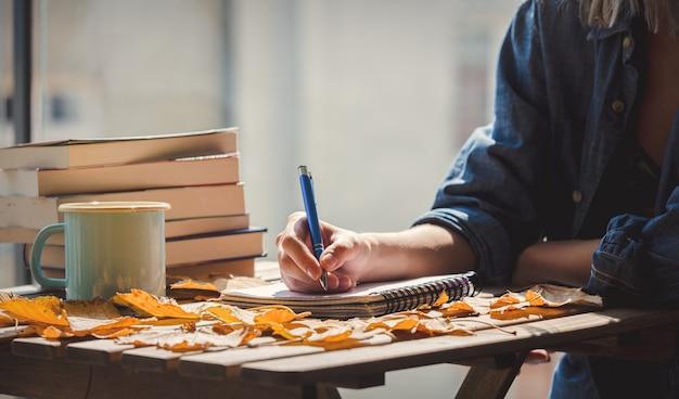 Mujer sosteniendo una taza y escribiendo algo