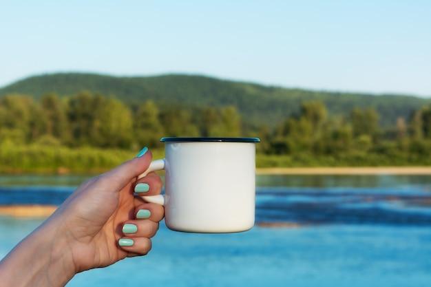 Mujer sosteniendo la taza de esmalte con vista al río
