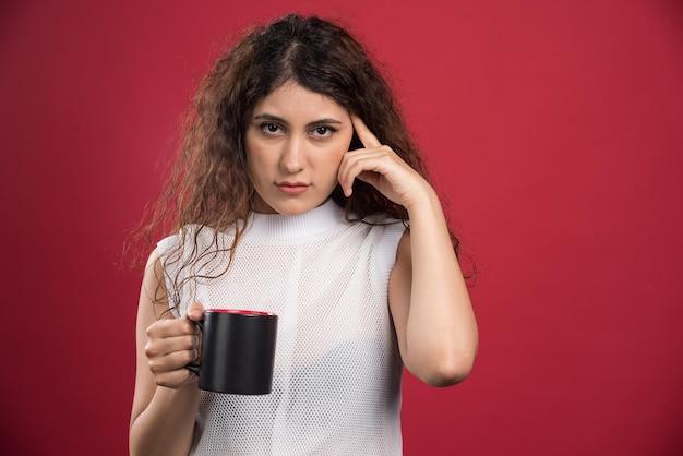 Mujer sosteniendo taza oscura caliente en rojo