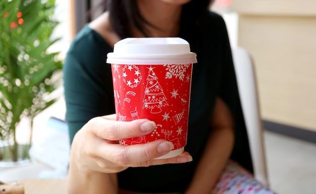 Mujer sosteniendo una taza de papel de patrón de navidad