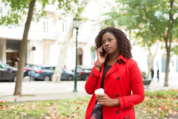 Mujer sosteniendo una taza de papel y tomando por teléfono celular