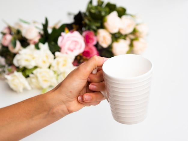 Mujer sosteniendo una taza con un ramo de rosas en el fondo