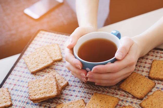 Mujer sosteniendo una taza de té o café caliente, acostarse junto a las galletas, primer plano