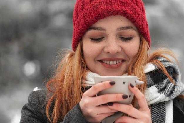 Mujer sosteniendo una taza de té y sonrisas