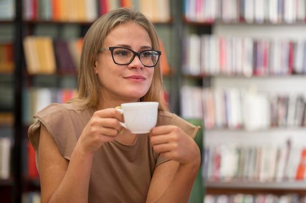 Mujer sosteniendo una taza de tiro medio