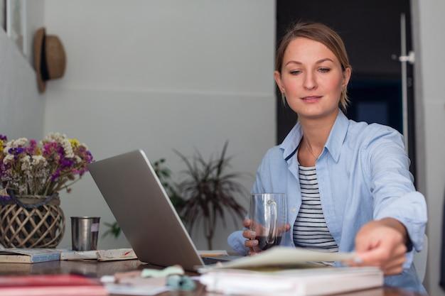 Mujer sosteniendo la taza y trabajando