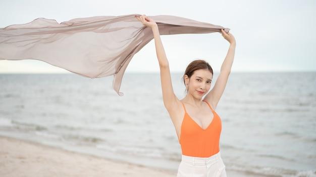 Mujer sosteniendo tela al viento en unas vacaciones en la playa. viajar y saludable.