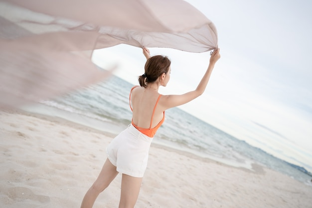 Mujer sosteniendo la tela al viento en unas vacaciones en la playa