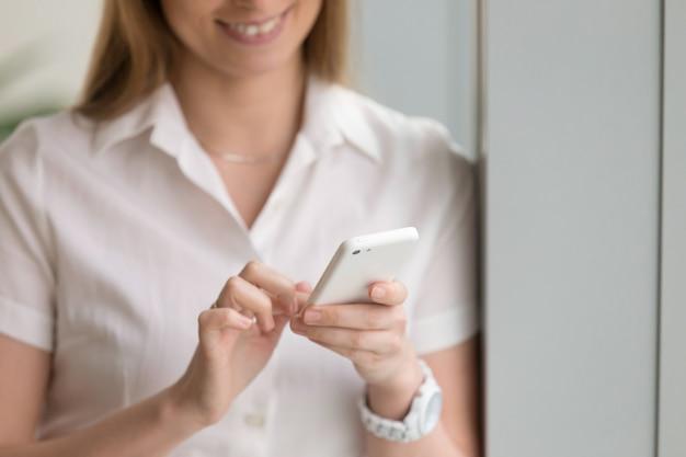 Mujer sosteniendo teléfono blanco, manos femeninas con teléfono inteligente, de cerca