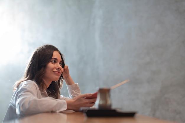 Mujer sosteniendo teléfono con cafetera defocused