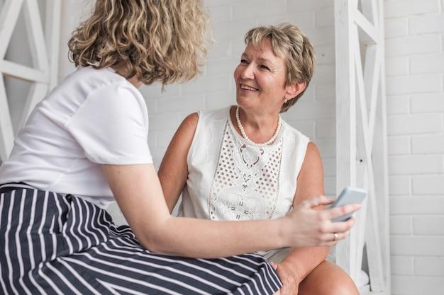 Mujer sosteniendo teléfono celular sentado con su madre en casa