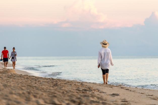 Mujer sosteniendo el teléfono celular y con sombrero de paja caminando en una playa al atardecer