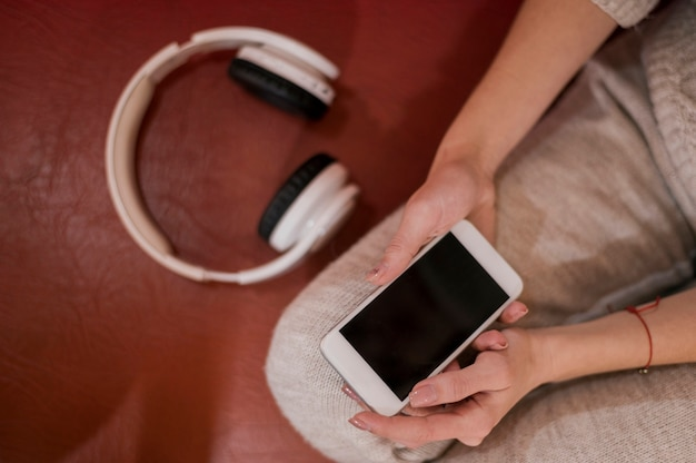 Mujer sosteniendo teléfono cerca de auriculares
