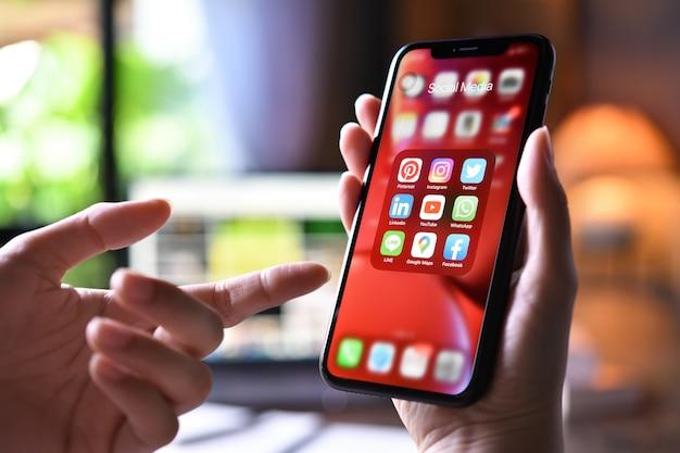 Mujer sosteniendo un teléfono inteligente con iconos de redes sociales en la pantalla en casa