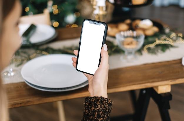 Mujer sosteniendo un teléfono inteligente con una maqueta de pantalla blanca en casa junto a la mesa festiva en la cocina.