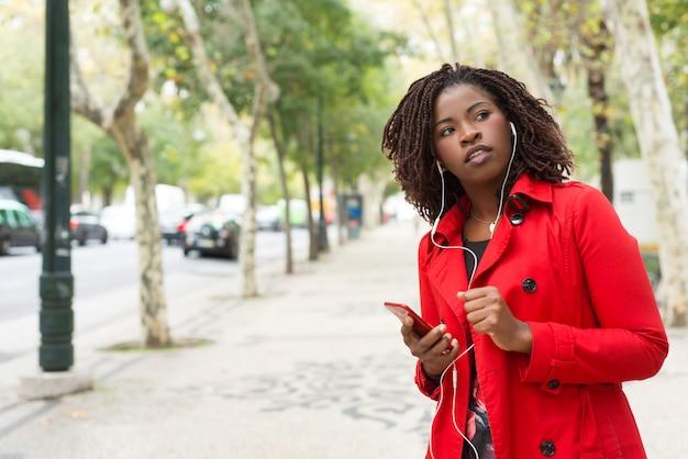 Mujer sosteniendo teléfono inteligente y mirando hacia el lado en la calle
