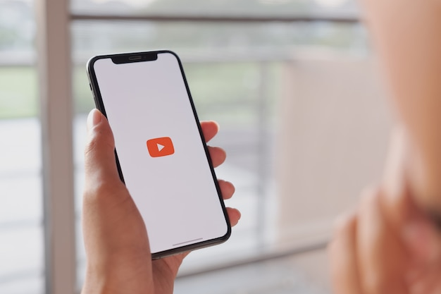 Mujer sosteniendo un teléfono inteligente con servicio de internet social youtube en la pantalla
