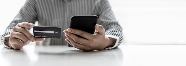 Mujer sosteniendo un teléfono inteligente y una tarjeta de crédito, está completando la información de su tarjeta de crédito para pagar las compras realizadas a través de la aplicación del teléfono inteligente. compras en línea y concepto de pago con tarjeta de crédito.