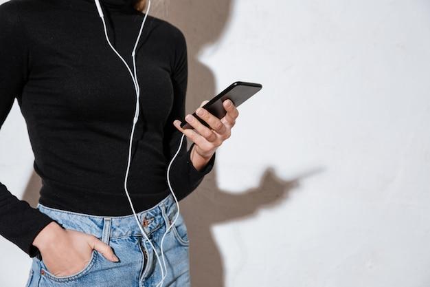 Mujer sosteniendo teléfono móvil con la mano en el bolsillo