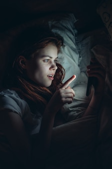 Mujer sosteniendo el teléfono en sus manos acostado en la cama por el estilo de vida nocturno.