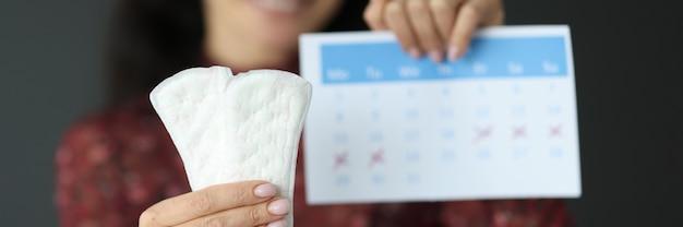 Mujer sosteniendo toallas sanitarias y calendario con primer plano de números rojos. concepto de ciclo menstrual
