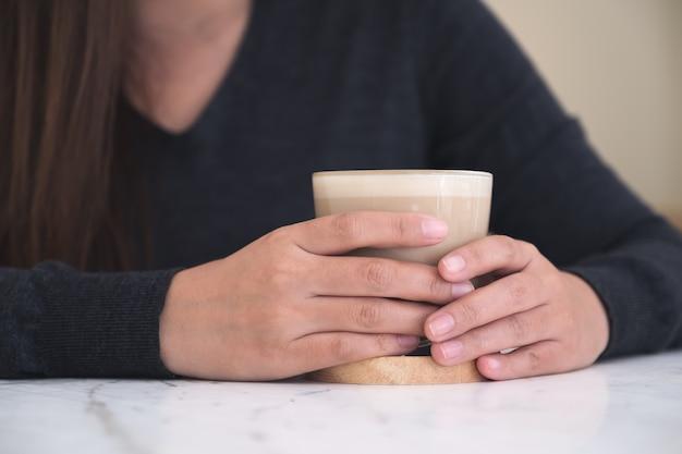 Una mujer sosteniendo y tomando café en la cafetería