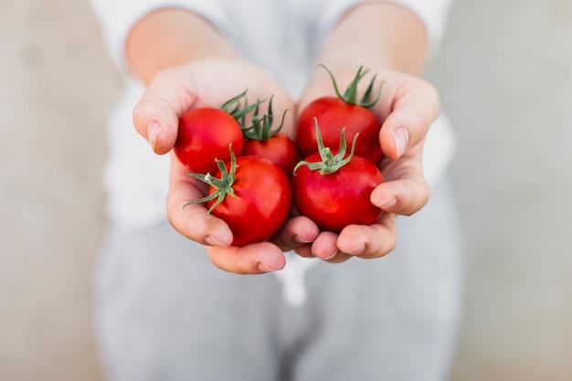 Mujer sosteniendo tomates en sus manos