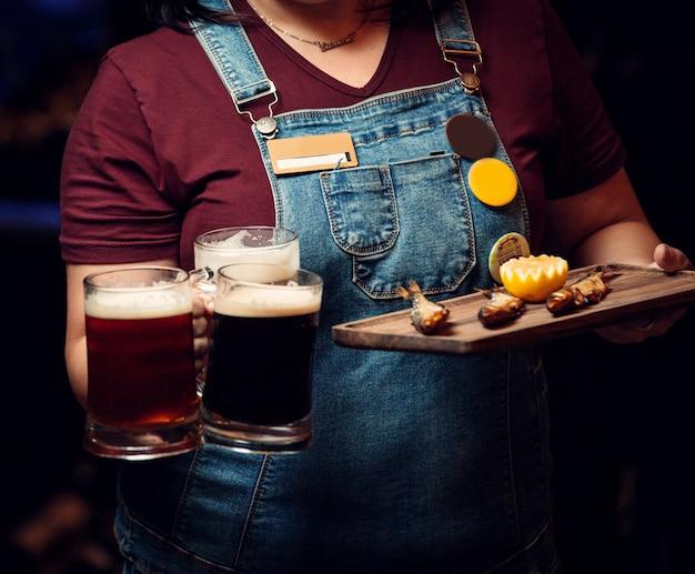 Mujer sosteniendo tres jarras de cerveza y plato de pescado ahumado con limón