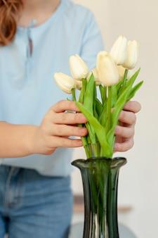 Mujer sosteniendo tulipanes de cerca
