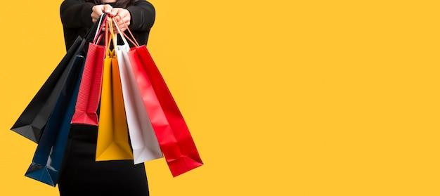 Mujer sosteniendo varias bolsas de compras espacio de copia