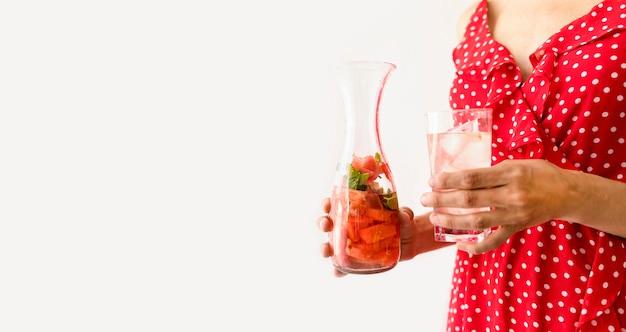 Mujer sosteniendo un vaso con agua y sandía copia espacio